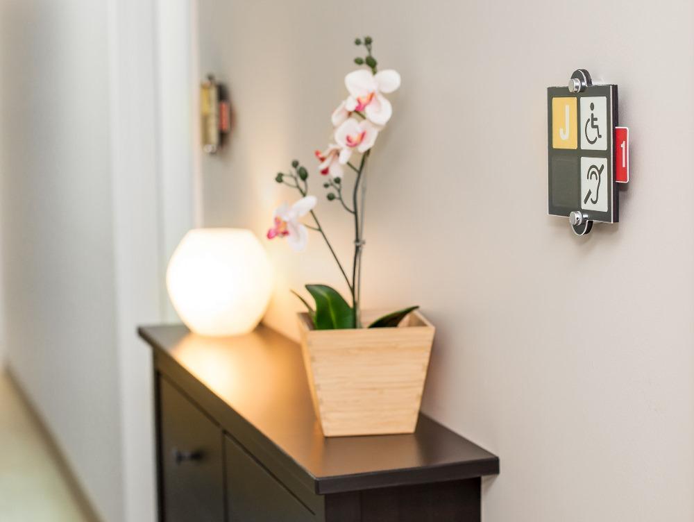 Une plaquette signalétique est apposée à côté de la porte des résidents afin d'afficher leurs limitations fonctionnelles et d'ainsi faciliter les interventions et les évacuations d'urgence.